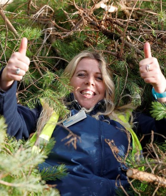 Happy lady laying in hedge with her thumbs up.
